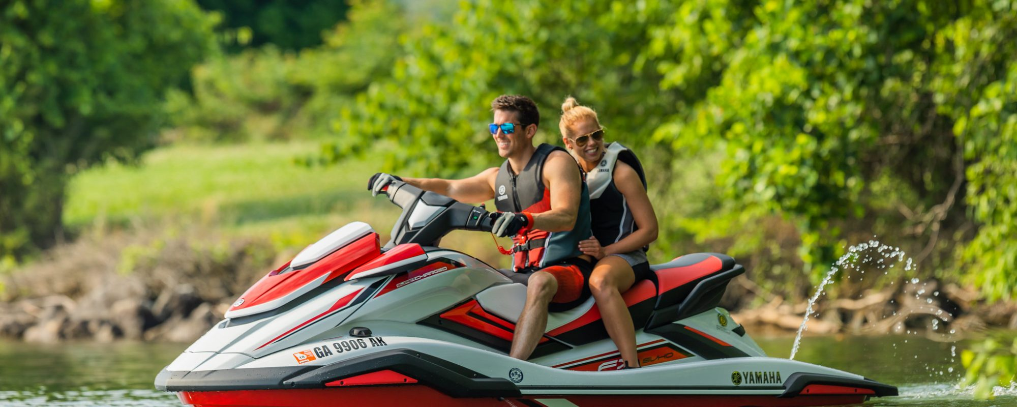 A couple sitting on a Yamaha Wave runner smiling on the lake